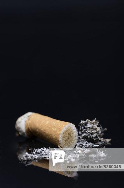 Verbrannte Zigarette mit Asche auf schwarzem Hintergrund  Nahaufnahme