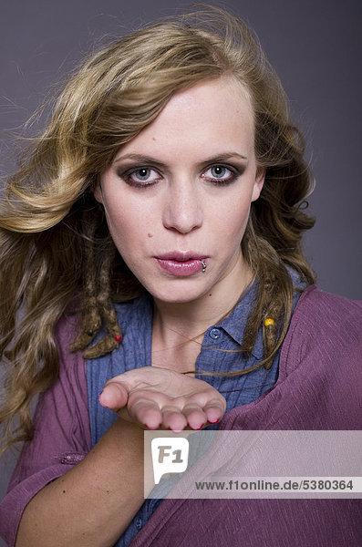 Junge Frau bläst Kuss vor violettem Hintergrund  Portrait  Mund