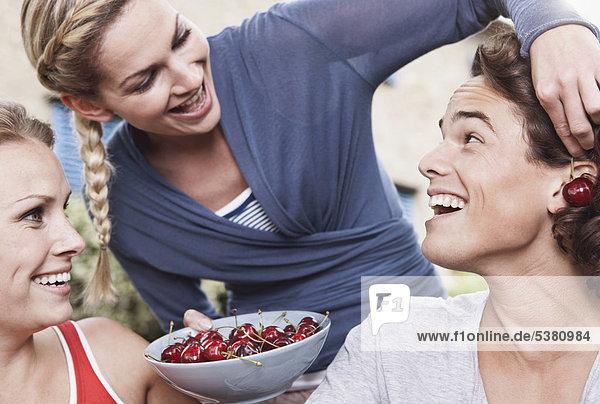 Italien  Toskana  Magliano  Junger Mann und junge Frauen halten Schale mit Kirschen und haben Spaß  lächeln