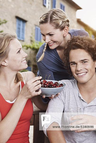 Italien  Toskana  Magliano  Junger Mann und Frauen mit Kirschenschale  lächelnd