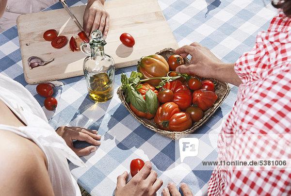 Italien  Toskana  Magliano  Junge Frau beim Tomatenschneiden mit Freunden im Vordergrund