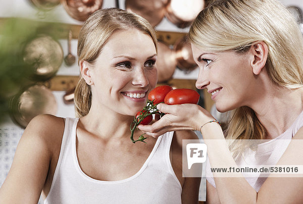 Italien  Toskana  Magliano  Zwei junge Frauen mit Tomaten in der Küche  lachend