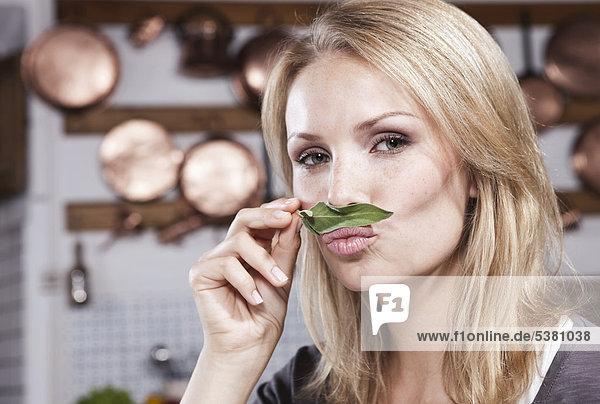 Italien  Toskana  Magliano  Nahaufnahme einer jungen Frau  die Basilikumblätter in der Küche riecht  Portrait