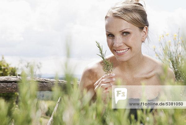 Italien  Toskana  Magliano  Nahaufnahme der Rosmarinpflanze vor der Frau  lächelnd  Portrait