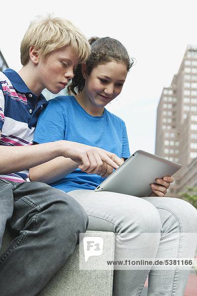 Deutschland  Berlin  Teenager-Paar mit digitalem Tablett in der Stadt