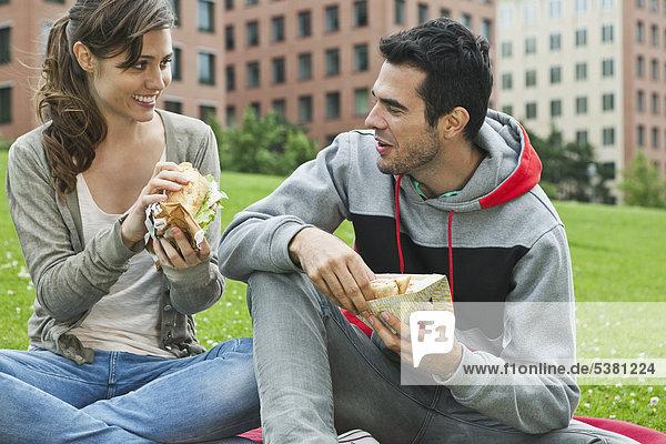 Deutschland  Berlin  Paar beim Essen im Park