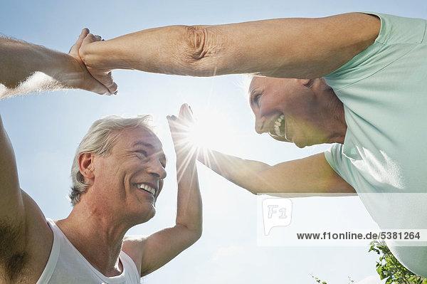 Mann und Frau trainieren im Garten  lächelnd
