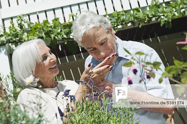 Reifer Mann und ältere Frau im Garten  lächelnd