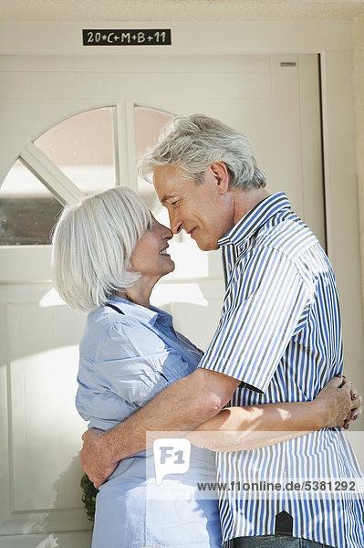 Mann und Frau umarmen sich an der Haustür
