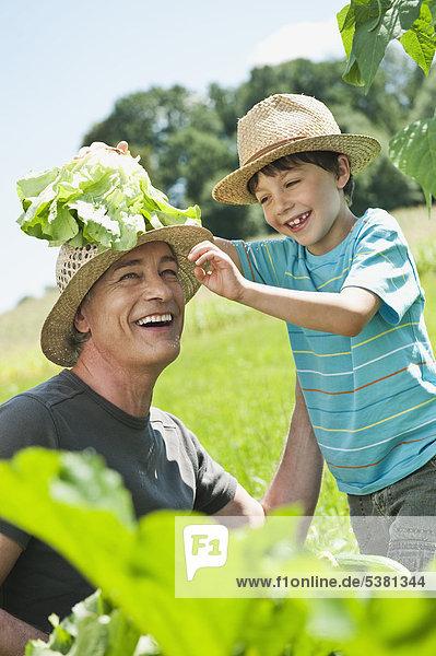 Deutschland  Bayern  Großvater mit Enkel im Gemüsegarten  lächelnd
