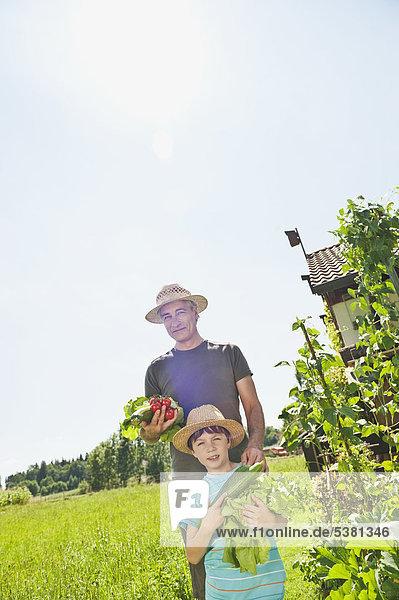 Deutschland  Bayern  Großvater mit Enkel im Gemüsegarten  lächelnd  Portrait
