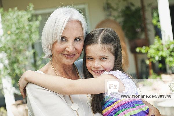 Deutschland  Bayern  Enkelin umarmt Großmutter  lächelnd  Portrait