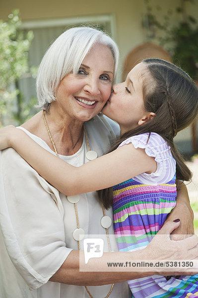Deutschland  Bayern  Enkelin küsst Großmutter im Garten