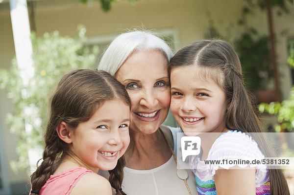 Deutschland  Bayern  Enkelinnen und Großmutter lächelnd  Portrait