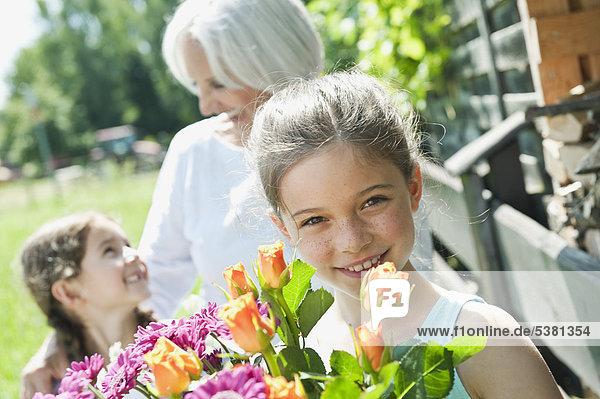 Deutschland  Bayern  Enkelinnen und Großmutter im Garten  lächelnd