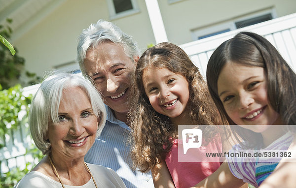 Deutschland  Bayern  Großeltern mit Tochter im Vordergrund  lächelnd  Portrait