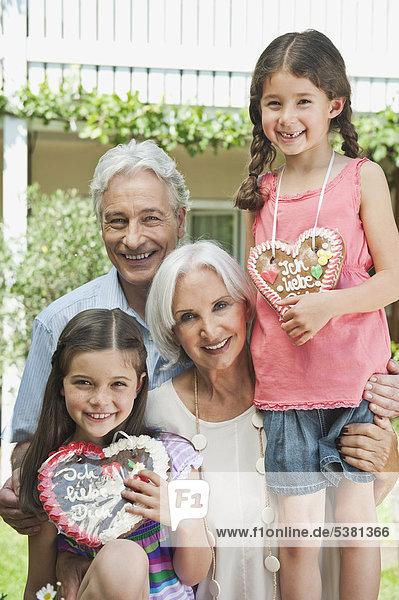 Deutschland  Bayern  Großeltern mit Enkelin mit Lebkuchen  lächelnd  Portrait