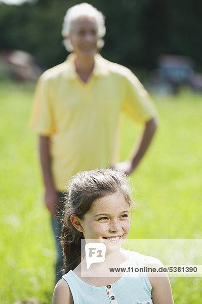 Mädchen lächelt mit Großvater im Hintergrund