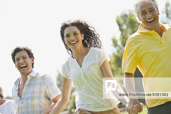 Mann und Frau laufen im Gras  lächelnd