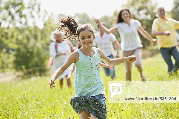 Deutschland  Bayern  Familie beim Picknick gemeinsam im Gras laufen