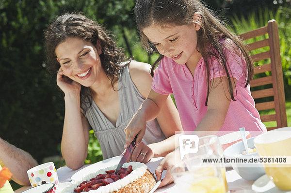 Mutter schaut Mädchen beim Kuchenschneiden an