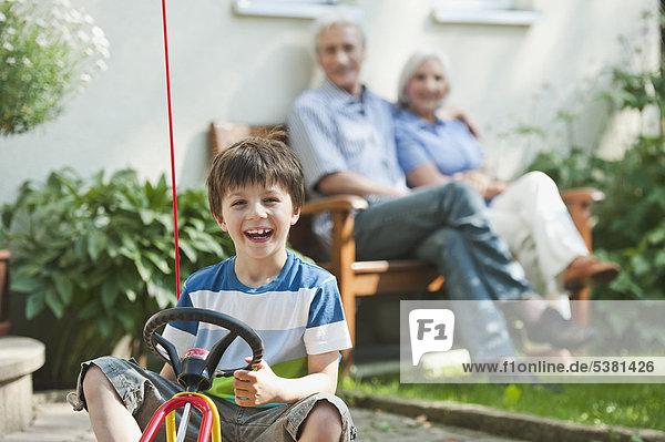 Junge auf Pedal Go-Kart mit Großeltern im Hintergrund