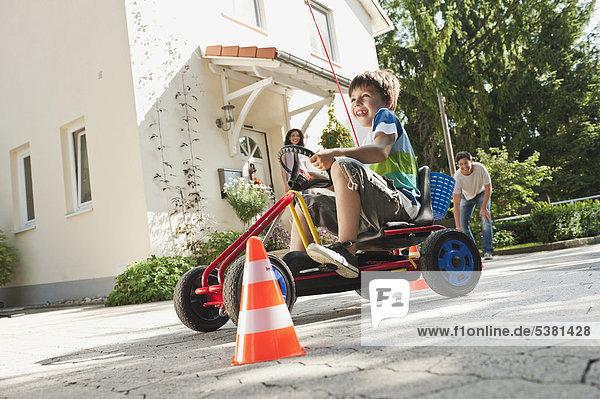 Junge Fahrpedal Go-Kart mit Eltern im Hintergrund