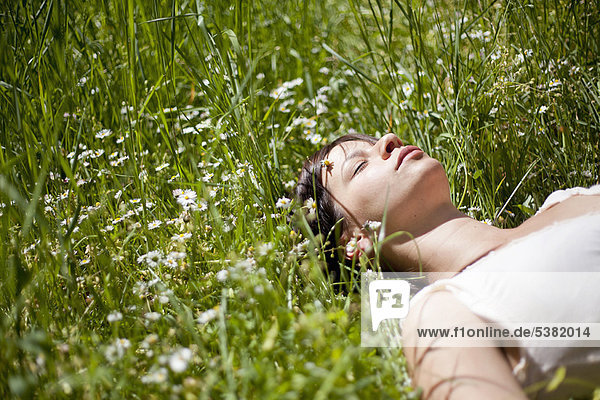 Frau schläft im hohen Gras