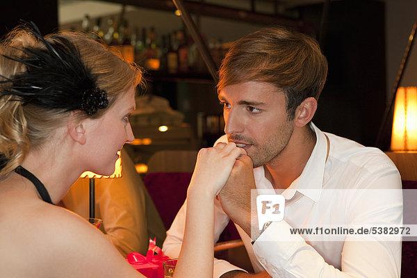 Mann küsst Freundin im Restaurant