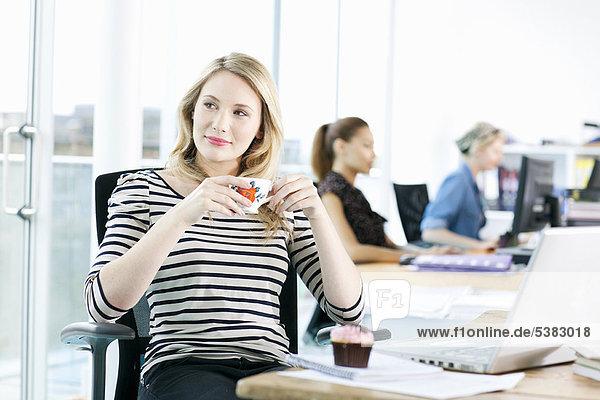Geschäftsfrau trinkt Kaffee am Schreibtisch