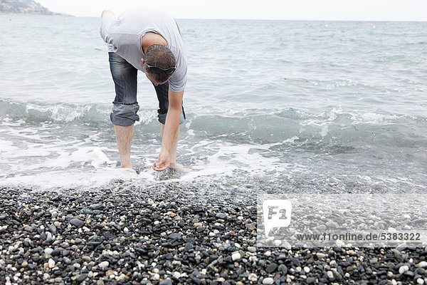 Mann sammelt Kieselsteine am felsigen Strand