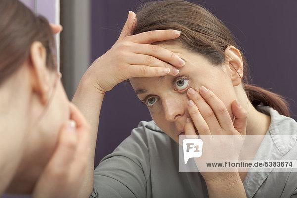 Frau untersucht ihr Auge im Spiegel