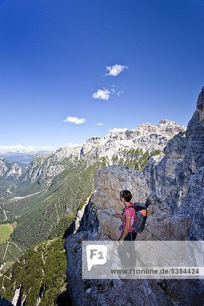 Bergsteigerin beim Aufstieg zum Monte Piano  Klettersteig im Hochpustertal  Dolomiten  hinten das Höhlensteintal  Südtirol  Italien  Europa