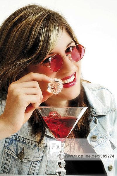 Junge Frau mit rosaroter Sonnenbrille und Cocktail