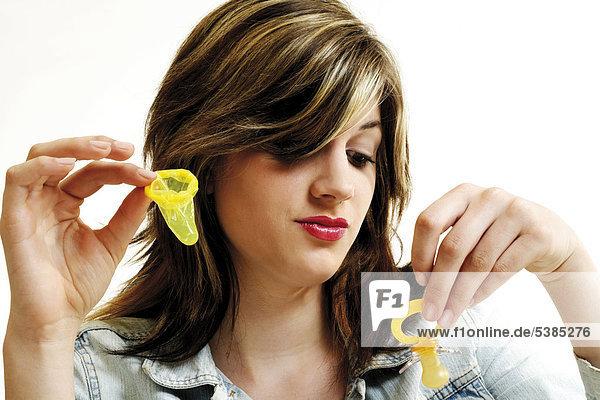 Junge Frau schaut skeptisch auf einen Schnuller und hält ein Kondom in der anderen Hand - Symbol Kind oder Karriere