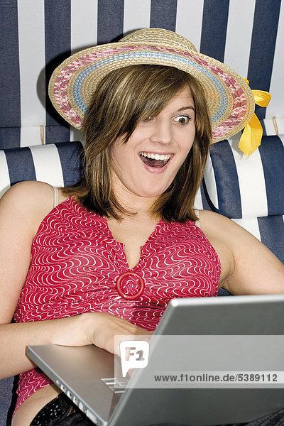 Junge Frau mit Strohhut  Sonnenbrille im Strandkorb mit Laptop