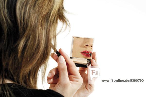 Junge Frau schaut in Makeup Spiegel