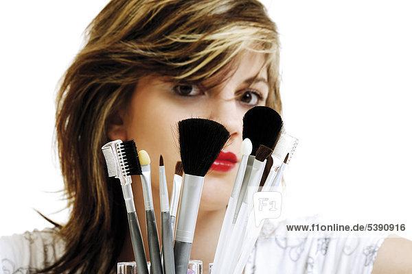 Junge Frau mit Makeup-Pinseln