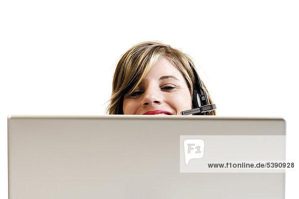 Junge Frau mit Headset hinter einem Laptop - Callcenter