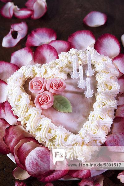 Kuchenherz Mit Marzipanrosen Und Brennenden Kerzen Auf Einem Bett Von  Rosenblättern