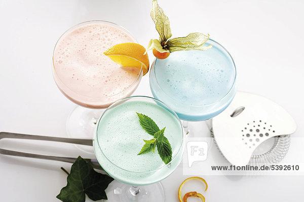 Cocktail glasses filled with peppermint cream liqueur  Blue Curacao cream liqueur and Campari orange cream liqueur