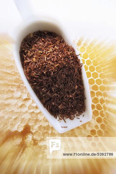 Rotbuschtee mit Vanille  Honigpollen und Mandeln vor Honigwabe