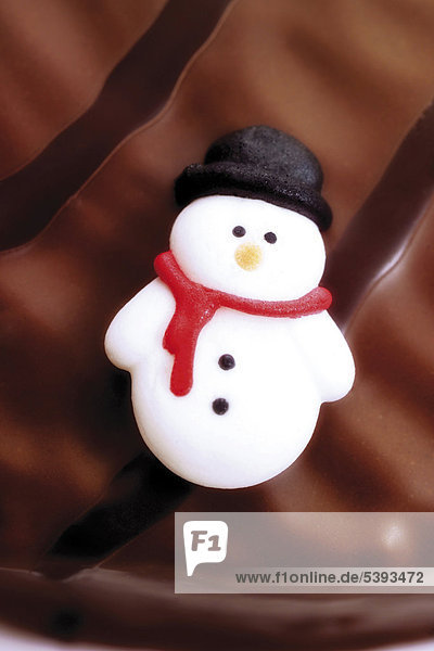Snowman Christmas sugar cookie on a chocolate icing cake