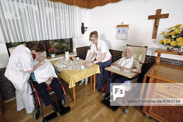 Im Altenheim  Pflegeheim  Pflegerin hilft einer Seniorin beim Essen