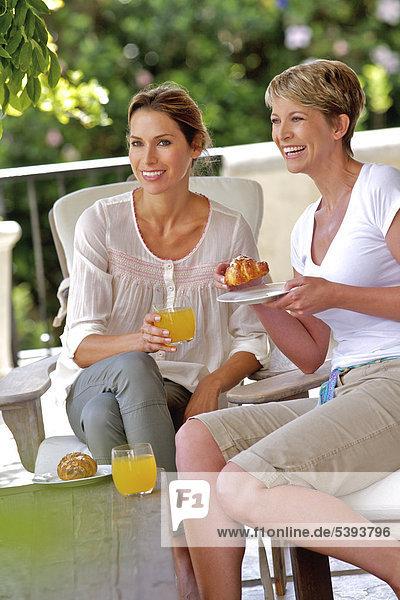 Zwei Frauen genießen Croissant und Saft