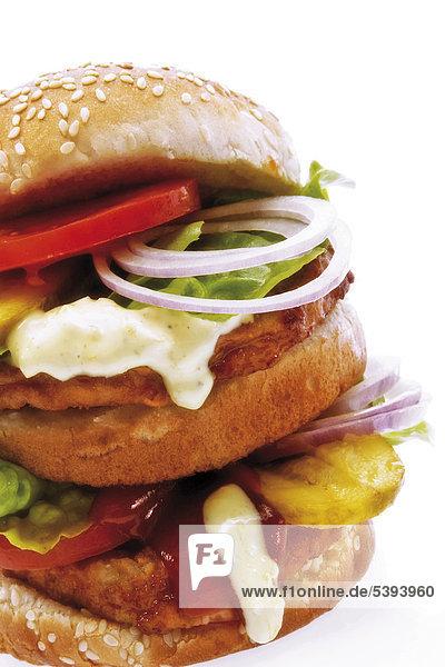 Doppelburger mit Tomate  Zwiebelringen  Gurken  Ketschup  Remoulade und Salat auf Sesambrötchen