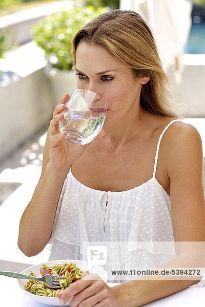 Reife Frau Essen Pasta und Trinkwasser außerhalb