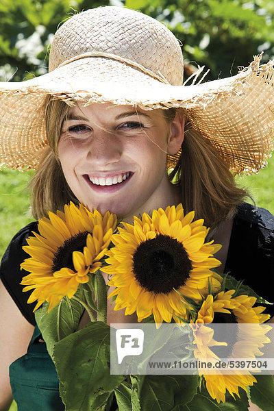 Mädchen mit Strohhut und Sonnenblumen