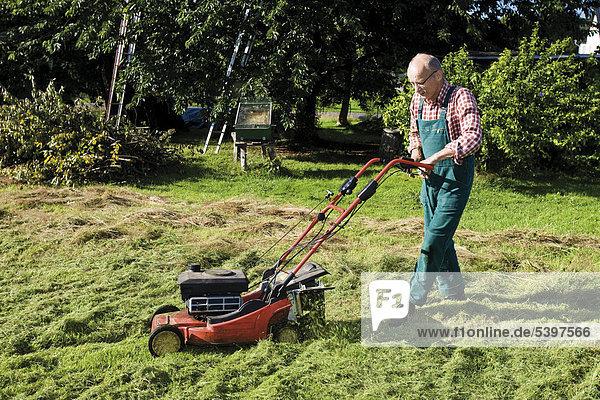 Gärtner mit Rasenmäher