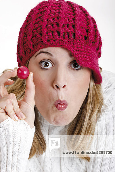 Young woman wearing a red woolen cap holding a ball of bubble gum